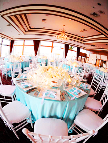 wedding reception tables with Tiffancy blue tablecloths, white Chiavari chairs with white cushions, and large square white chargers with Tiffany gifts tied with white bows, and white rose centerpieces